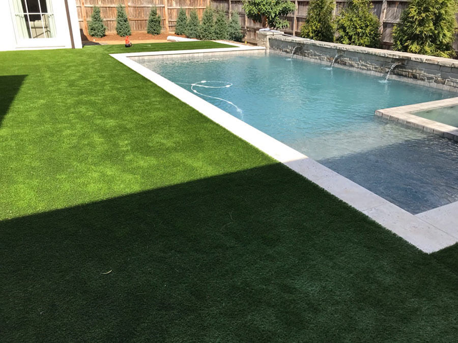 backyard pool surrounded by landscaping
